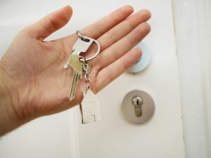 Hand holding house keys in front of a door